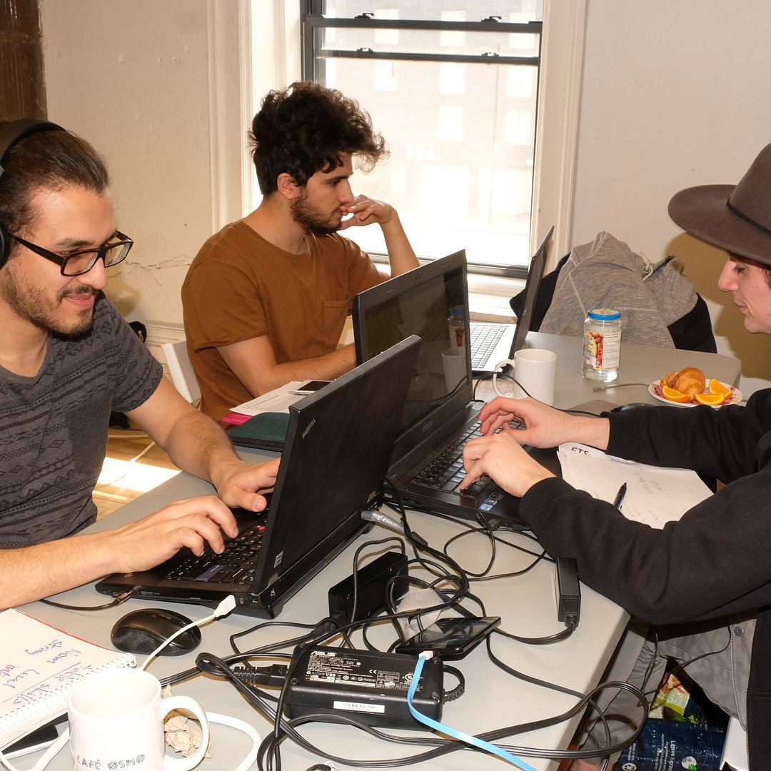 3 student working in a computer in a crowded space
